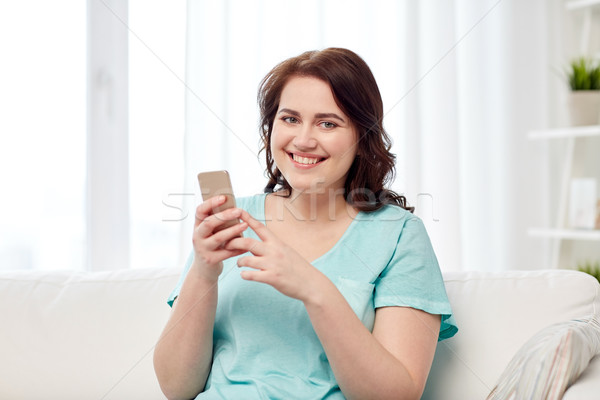 happy plus size woman with smartphone at home Stock photo © dolgachov