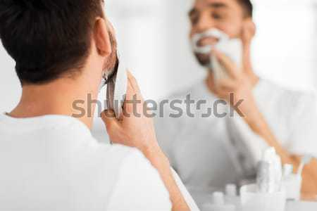 close up of man removing shaving foam from face Stock photo © dolgachov