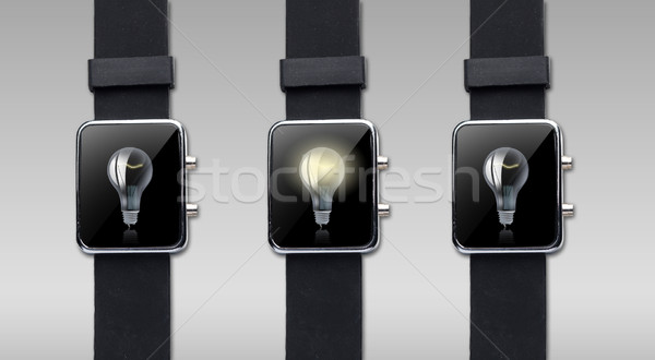 close up of smart watch with light bulb on screen Stock photo © dolgachov