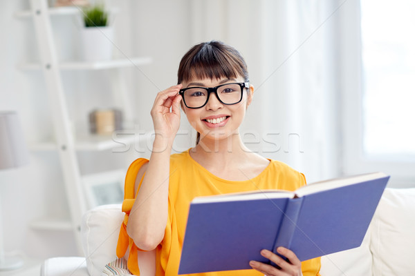 Stock photo: smiling young asian woman reading book at home