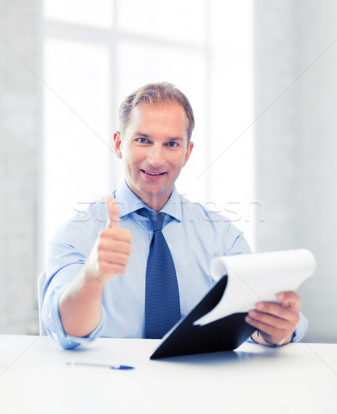 businessman with papers showing thumbs up Stock photo © dolgachov