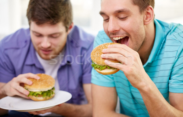 close up of friends eating hamburgers at home Stock photo © dolgachov
