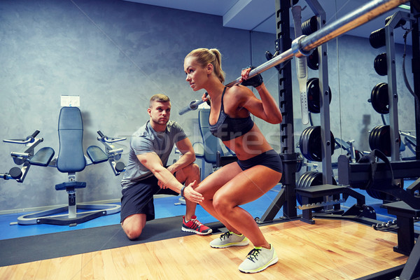 man and woman with bar flexing muscles in gym Stock photo © dolgachov
