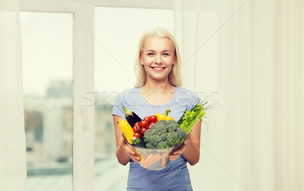 smiling young woman with vegetables at home Stock photo © dolgachov