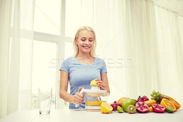 smiling woman squeezing fruit juice at home Stock photo © dolgachov