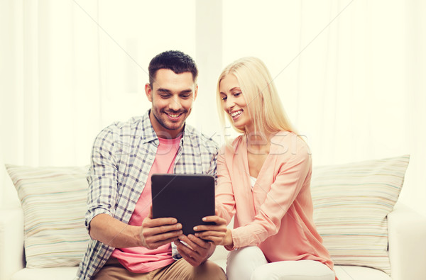 Stock photo: smiling happy couple with tablet pc at home