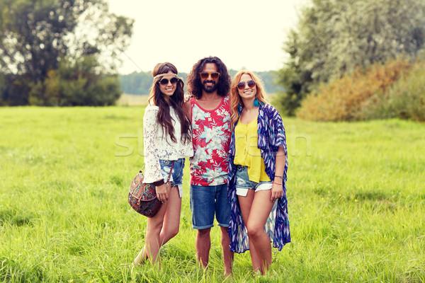 Mosolyog fiatal hippi barátok zöld mező Stock fotó © dolgachov