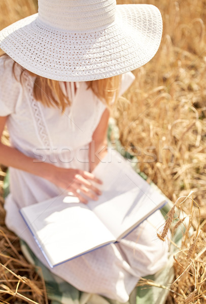 close up of woman reading book on cereal field Stock photo © dolgachov