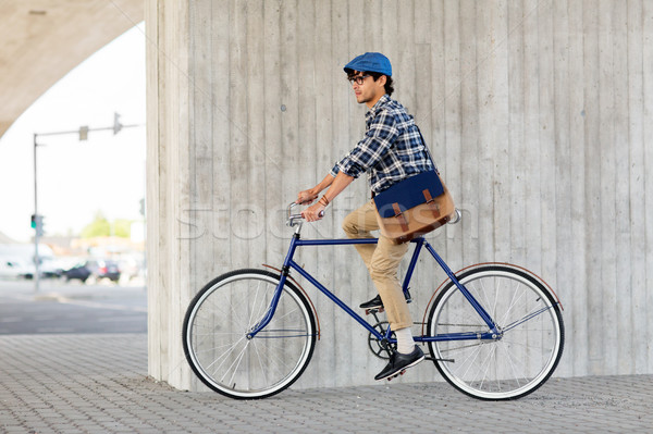 Stock photo: young hipster man with bag riding fixed gear bike