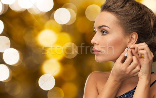 close up of woman fastening diamond earring Stock photo © dolgachov