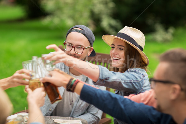 Stock photo: happy friends clinking glasses at summer garden