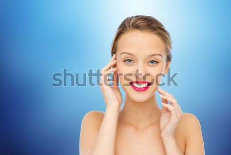 beautiful woman in black over blue background Stock photo © dolgachov