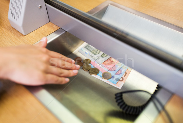 hand with cash money at bank office or exchanger Stock photo © dolgachov