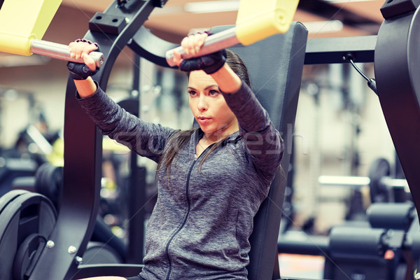 woman flexing muscles on chest press gym machine  Stock photo © dolgachov