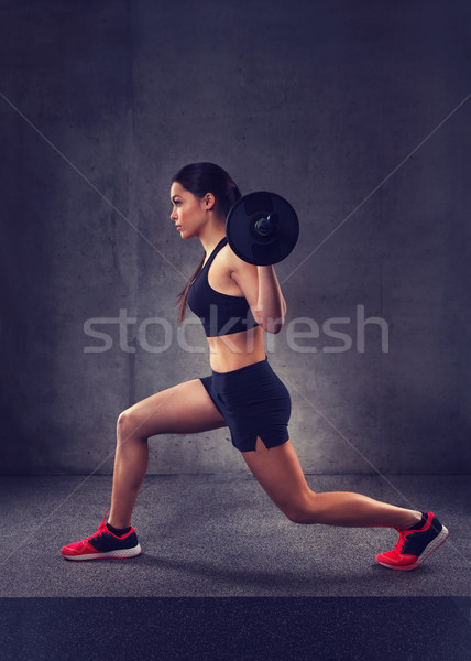 young woman flexing muscles with barbell in gym Stock photo © dolgachov