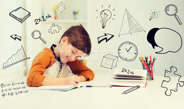 Mosolyog diák fiú ír notebook otthon Stock fotó © dolgachov