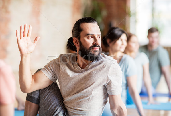 man with group of people doing yoga at studio Stock photo © dolgachov