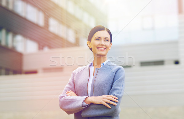 Stock photo: young smiling businesswoman over office building