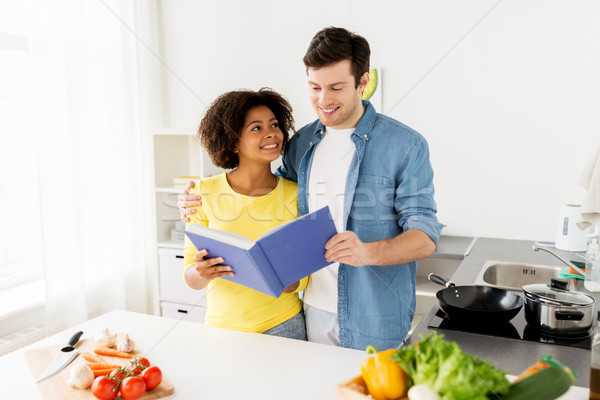 happy couple with cooking book at home kitchen Stock photo © dolgachov