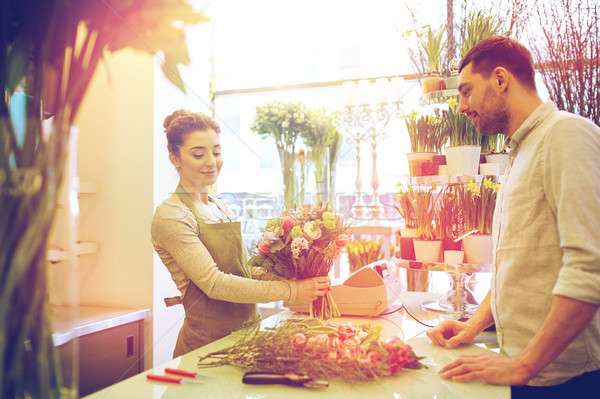 smiling florist woman and man at flower shop Stock photo © dolgachov