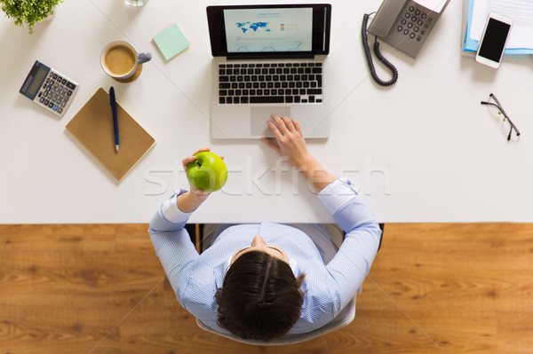 businesswoman with apple and laptop at office Stock photo © dolgachov