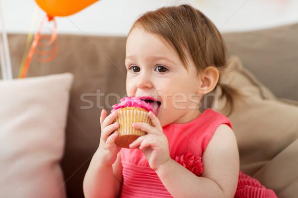 happy baby girl eating cupcake on birthday party Stock photo © dolgachov