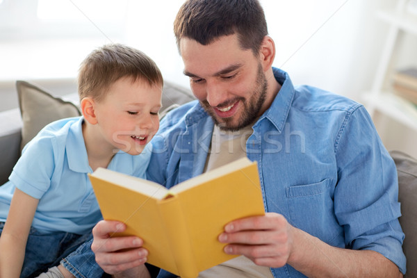 happy father and son reading book sofa at home Stock photo © dolgachov