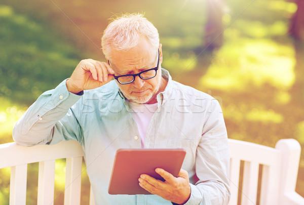senior man with tablet pc at summer park Stock photo © dolgachov