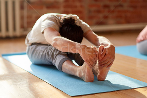 man doing yoga forward bend at studio or gym Stock photo © dolgachov