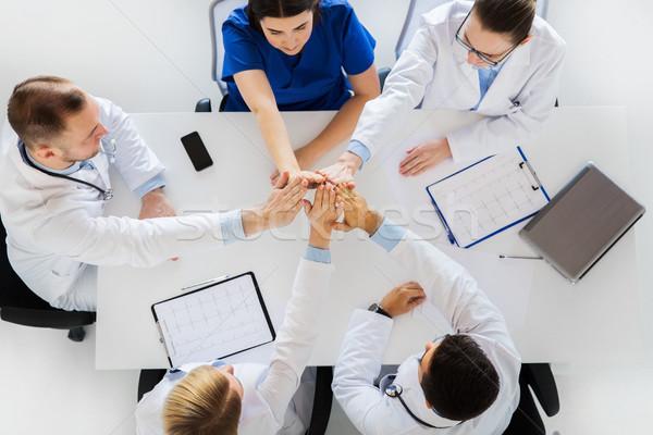 Groupe médecins high five table médecine Photo stock © dolgachov