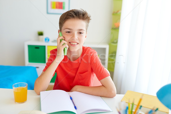 student boy calling on smartphone at home Stock photo © dolgachov