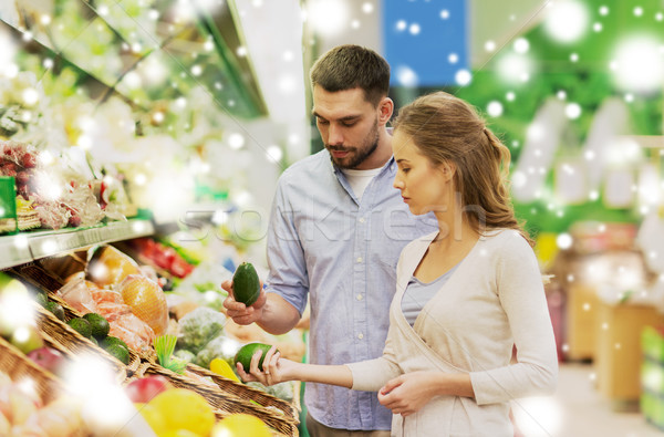 happy couple buying avocado at grocery store Stock photo © dolgachov