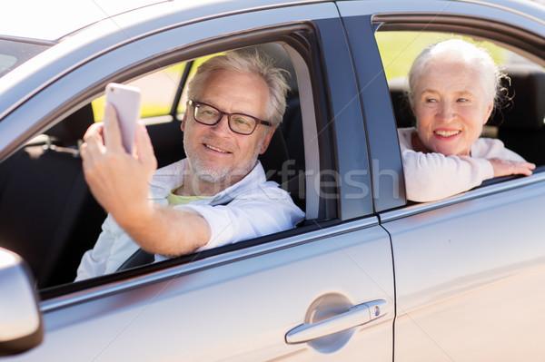 Stock photo: senior couple in car taking smartphone selfie