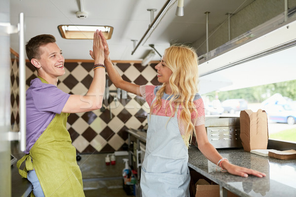 couple of sellers making high five at food truck Stock photo © dolgachov