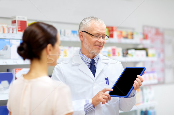 apothecary and customer with tablet pc at pharmacy Stock photo © dolgachov