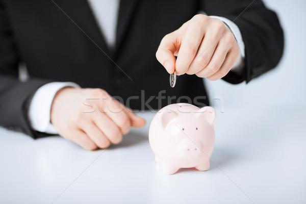 man putting coin into small piggy bank Stock photo © dolgachov