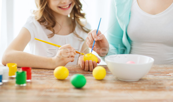 close up of little girl and mother coloring eggs Stock photo © dolgachov