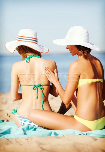 girls applying sun cream on the beach Stock photo © dolgachov