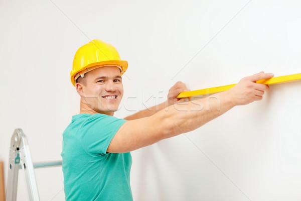 smiling man building using spirit level to measure Stock photo © dolgachov