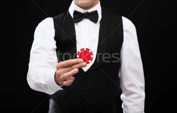 dealer holding red poker chip Stock photo © dolgachov