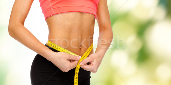 Stock photo: close up of female hands measuring waist