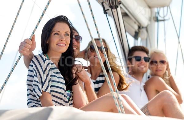 smiling friends sitting on yacht deck Stock photo © dolgachov