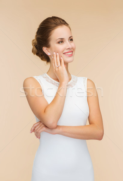 smiling woman in white dress with diamond ring Stock photo © dolgachov