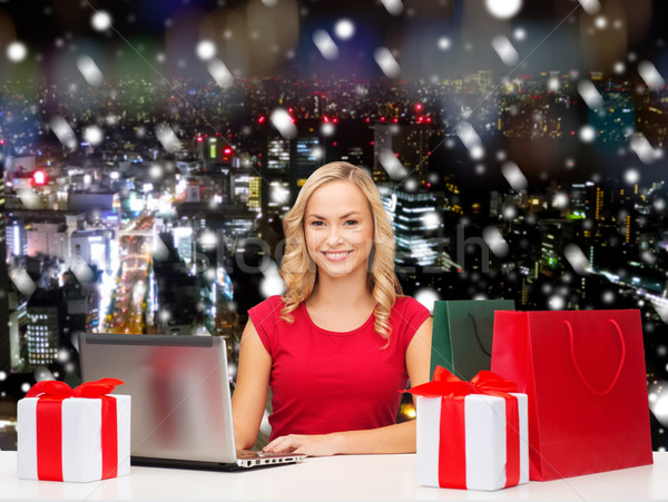 smiling woman in red shirt with gifts and laptop Stock photo © dolgachov
