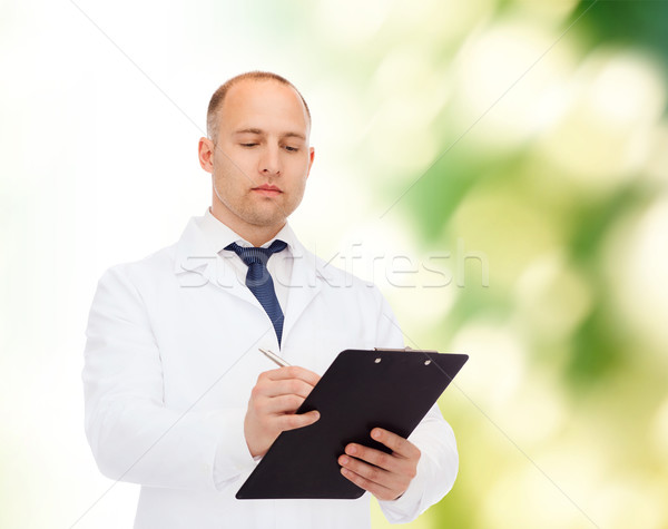 serious male doctor with clipboard Stock photo © dolgachov