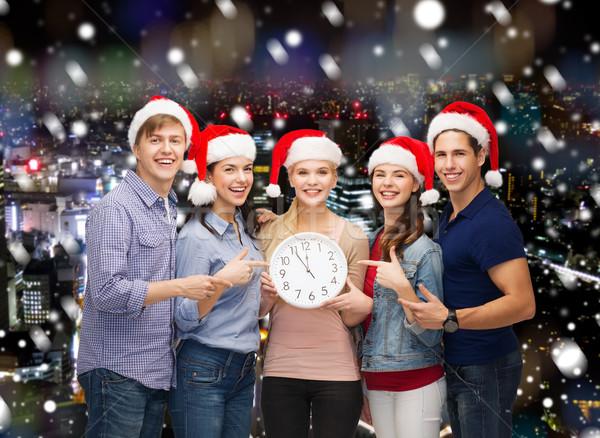 group of teenagers in santa helper hats with clock Stock photo © dolgachov