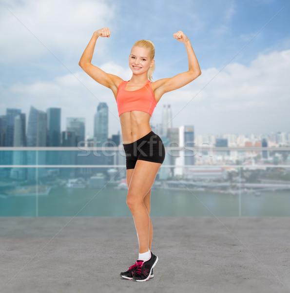 Glimlachend vrouw tonen biceps fitness Stockfoto © dolgachov