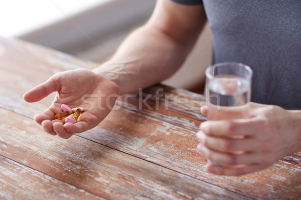 close up of male hands holding pills and water Stock photo © dolgachov