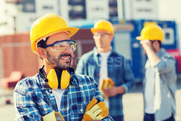 Stock photo: group of smiling builders in hardhats outdoors
