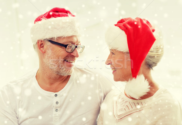 happy senior couple in santa helper hats at home Stock photo © dolgachov